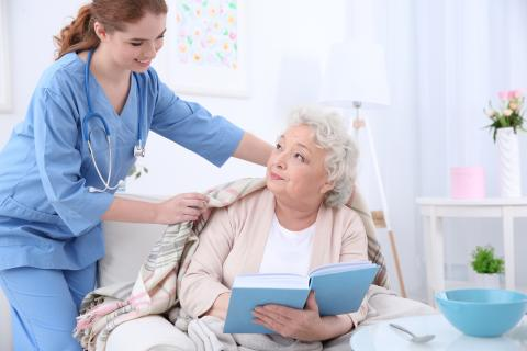Una donna anziana allettata, assistita dal personale della RSA